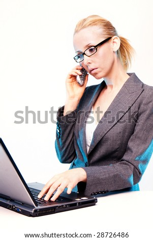 blonde businesswoman using laptop computer and mobile phone  at work - stock photo