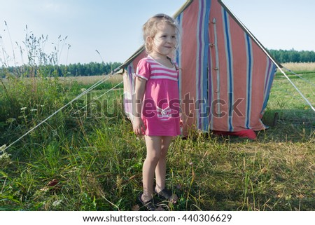 Blonde camper girl enjoying outdoors leisure near striped vintage canvas tent - stock photo