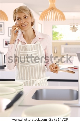 Blonde casual caucasian housewife in bright kitchen with mobile phone, indoors, standing, wooden spoon in hand, cooking, wearing apron. - stock photo