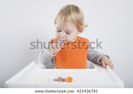 blonde caucasian baby seventeen month age orange bib grey sweater eating meal with her hand in white high-chair - stock photo