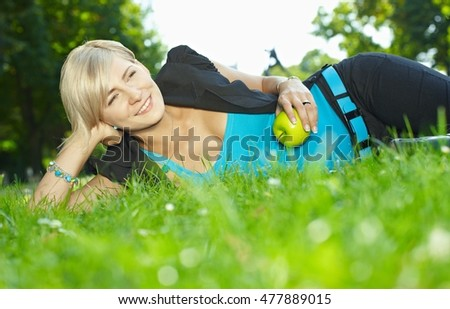 Blonde caucasian businesswoman lying grass at outdoor park with apple in hand. Happy, smiling, relaxed. Close to ground shot.