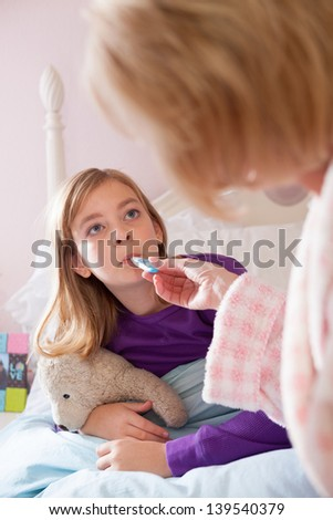 Blonde caucasian mother wearing bathrobe, takes teen-aged daughter's temperature while on her bed, looking at each other. - stock photo