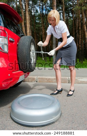 Blonde changing tire alone on a road - stock photo