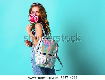 Blonde   cheerful girl posing with pink lollipop in stylish summer outfit . Happy teenager posing in studio with silver backpack. Bright positive colors.  - stock photo