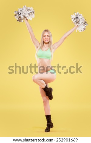 blonde cheerleader with pompoms on bright background