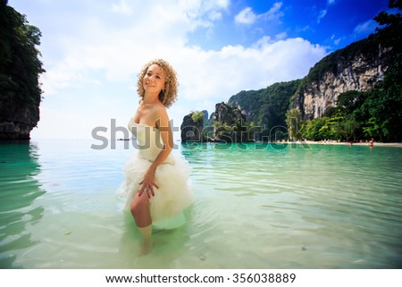 blonde curly bride in fluffy wedding dress stands in transparent shallow azure sea against green rocky islands