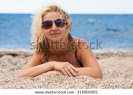 blonde curly-haired woman in glasses lying on the sand at the beach - stock photo