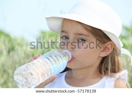 Blonde cute little girl drinking water - stock photo