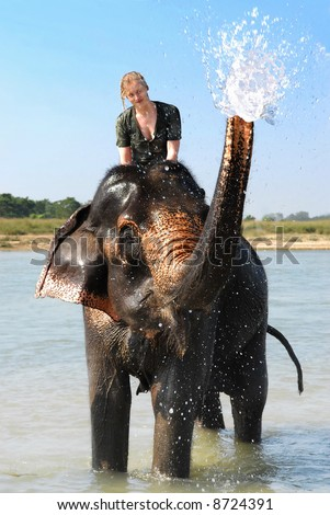 blonde european girl getting a wet t-shirt on an elephant in asia - stock photo