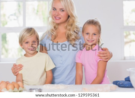 Blonde family smiling at the camera with baking tools - stock photo