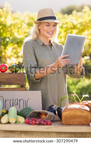 Blonde farmer using a tablet over a table of local food - stock photo