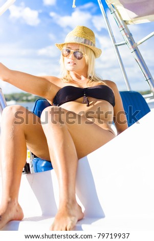 Blonde Female Boat Skipper Sitting Unwinding Resting And Tanning In The Summer Sun While On A Boating Holiday In A Scene Of Beauty And Holidays - stock photo