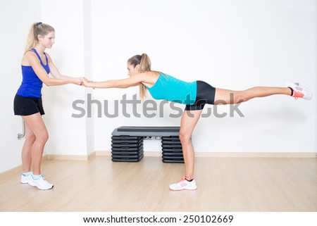 blonde female coach helping with balance exercise - stock photo