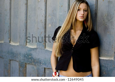 Blonde female fashion model in sexy clothing against blue door