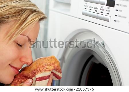 blonde female is smelling freshly washed laundry - stock photo