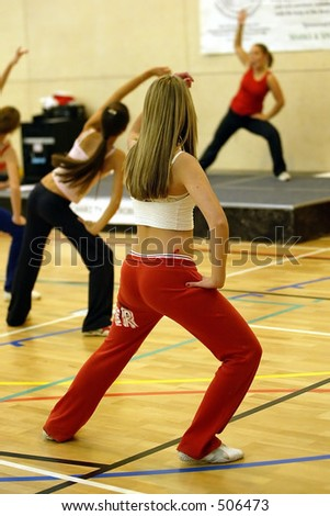 blonde female stretching in an aerobics exercise class with instructor in background - stock photo