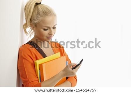 Blonde female student using mobile phone, holding folders. - stock photo