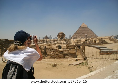 Blonde female turist takin picture of the Sphinx and the pyramids of Khafre (Chephren) and Menkaur (Mycerinus) in Giza - Cairo, Egypt - stock photo