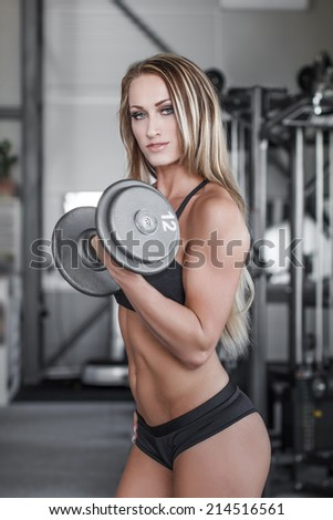 Blonde fitness model workout with dumbbell, gym - stock photo