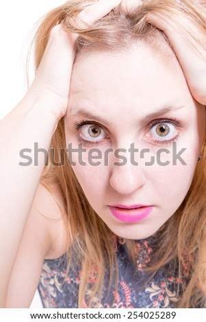 Blonde girl a little worried, holding her face in astonishment - stock photo