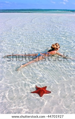 Blonde girl and red starfish on the beach