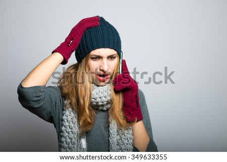 blonde girl anxiously on the phone, Christmas concept, studio photo isolated on a gray background