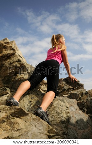 Blonde girl climbing on the rock on background - stock photo