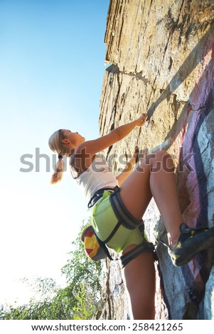 Blonde girl climbing on the rock on background blue sky