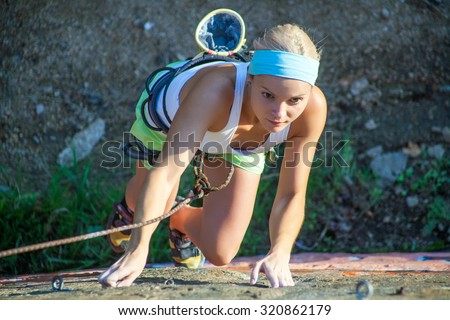 Blonde girl climbing on the rock. Top view