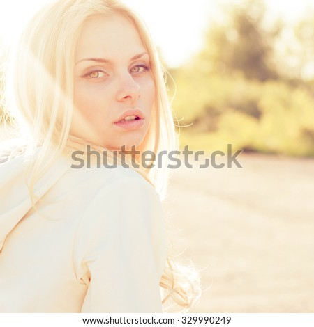 Blonde girl close-up portrait in sun-rays - stock photo