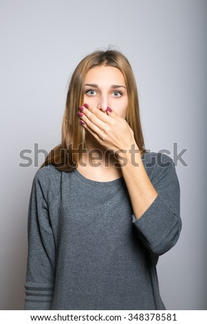 blonde girl covers her mouth with her hands, did not want to speak with clean skin, lifestyle concept studio photo isolated on a gray background - stock photo