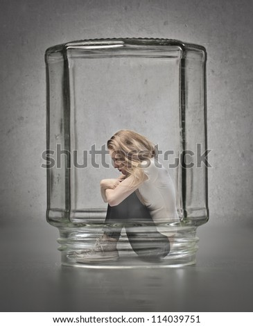 Blonde girl crouched in a glass container