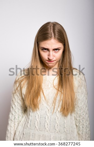 blonde girl dissatisfied with a serious face, isolated