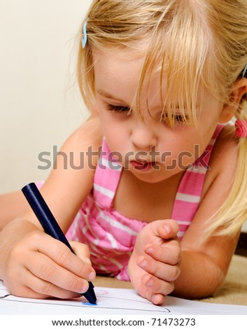 blonde girl drawing with crayons in school (focus on hand)