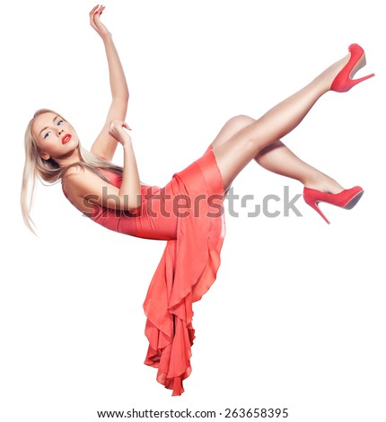 Blonde girl hangs in the air and falls. Her coral-colored dress and shoes. - stock photo