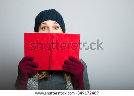 blonde girl hiding behind the book, Christmas and New Year concept, studio photo isolated on a gray background - stock photo