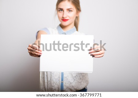 blonde girl holding a blank sheet of paper, isolated - stock photo