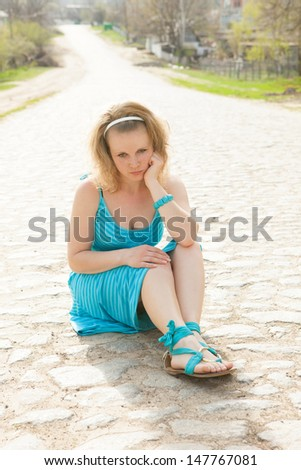 blonde girl in a blue dress sitting on the road