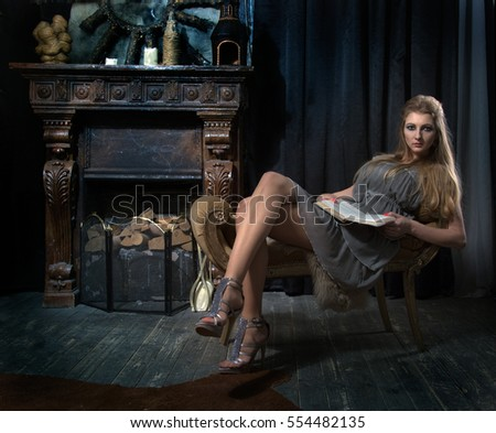 Blonde girl in a gray dress sitting on a couch and read a book by the fireplace