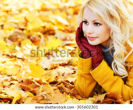 Blonde girl in Autumn Park with Maple leaves. Fashion Beautiful Woman with leather gloves. Fall