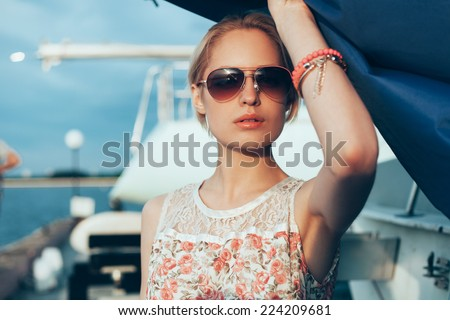 Blonde girl in flower dress and sunglasses holding  boat sails at sunset. Outdoor lifestyle portrait of woman - stock photo