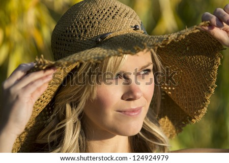 Blonde girl in straw hat outdoors - stock photo