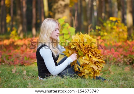 Blonde girl in the autumn park makes a wreath of autumn maple leaves - stock photo