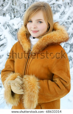 Blonde girl in winter forest