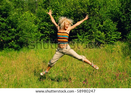 Blonde girl jumping on a green meadow - stock photo