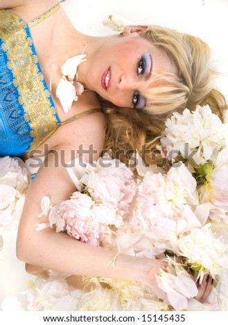 Blonde girl laying on the peony - stock photo