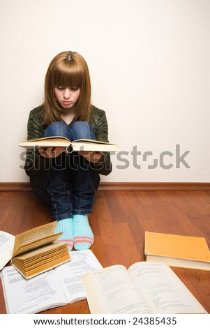 Blonde girl learning for her exam, with books spread over the floor