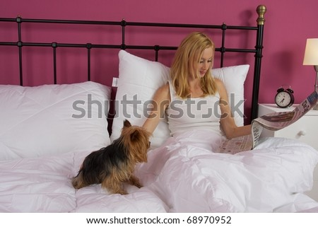 Blonde girl lying in bed reading a newspaper with small dog