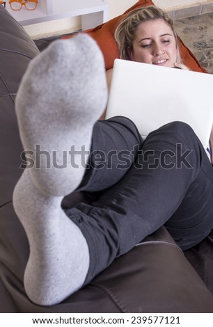 Blonde girl lying on sofa using computer