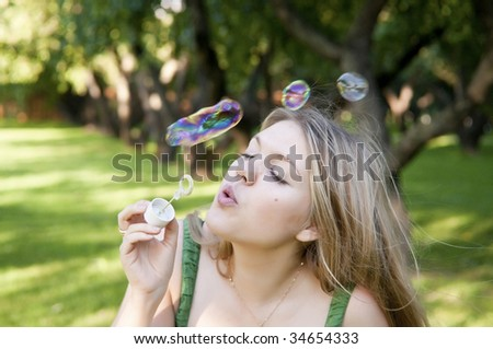 blonde girl makes soap bubbles